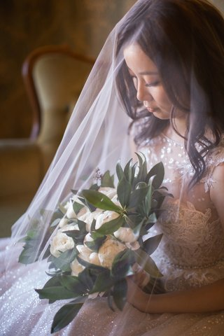 asian-bride-wearing-blusher-veil-draping-delicately-over-the-bridal-bouquet