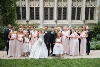 bride-in-ines-di-santo-gown-bridesmaids-in-long-pink-dresses-groomsmen-in-tuxedos-in-courtyard