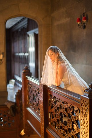 veiled-bride-balcony-looking-down-berta-bridal-veil-wedding-styled-shoot-vintage-hempstead-house-ny