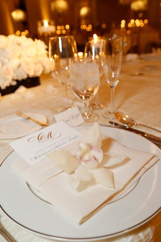 wedding-reception-place-setting-with-white-china-charger-linen-napkin-white-orchid-menu