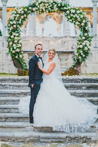 bride-in-lace-a-line-isabelle-armstrong-gown-with-groom-in-front-of-circular-ceremony-arch