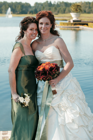 bride-in-ball-gown-with-sage-sash-in-front-of-lake-with-mother-of-bride-in-green-dress