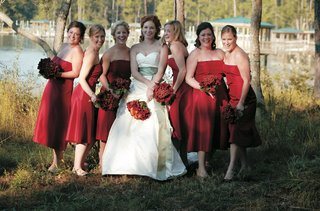 bride-in-front-of-lake-with-bridesmaids-in-red-bridesmaid-dresses