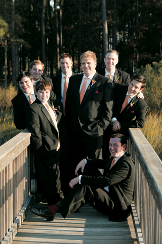 groom-and-groomsmen-in-black-suits-with-red-orange-ties