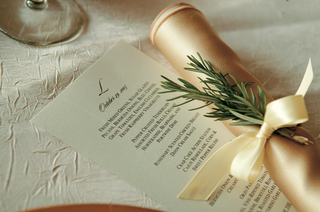 white-stationery-with-black-monogram-next-to-gold-napkin-and-rosemary-sprig