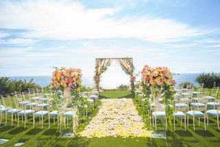 outdoor-wedding-ceremony-yellow-flower-petal-aisle-light-blue-guest-seating-chameleon-chair