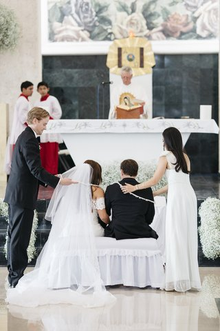 catholic-wedding-ceremony-with-a-pearl-lasso-being-put-on-the-bride-and-groom