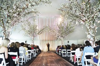 white-tent-wedding-ceremony-with-wood-aisle-and-tree-decor