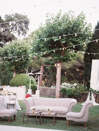 outdoor-lounge-area-with-tan-furniture-small-glass-coffee-tables-low-florals-under-string-of-lights