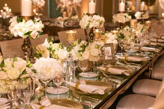long-mirror-wedding-reception-table-with-gold-candles-low-rose-centerpieces-gold-charger-gold-rim
