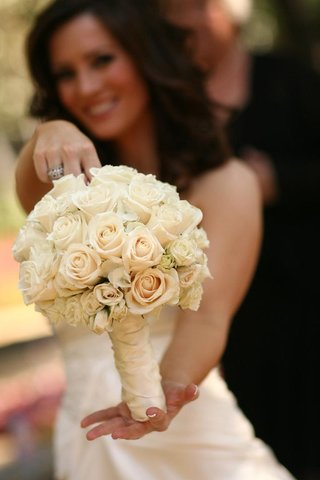 bride-holding-vory-roses-wrapped-in-ribbon