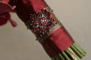 red-ribbon-around-bouquet-stems-and-jewel-brooch