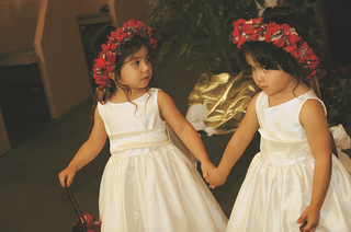 two-flower-girls-hold-hands-in-white-dresses-and-red-flower-crowns