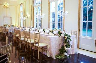 wedding-reception-gold-chairs-blush-linens-long-table-flower-runner-on-floor-gold-details-ballroom