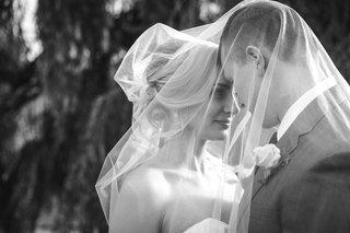 black-and-white-photo-of-couple-underneath-veil-newlyweds-wedding-portland-oregon-outdoors-strapless