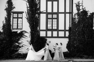 black-and-white-photo-of-bride-in-a-line-gown-veil-being-held-by-bridesmaids-maid-of-honor-outside