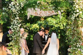 wedding-ceremony-greenery-woods-area-with-groom-touching-eyes-parents-on-both-sides-jewish-ceremony