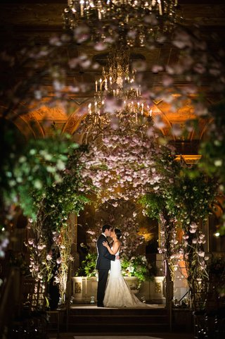 couple-kissing-beneath-floral-altar-in-ballroom