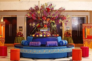 round-couch-in-royal-blue-with-blue-and-purple-cushions-is-topped-with-candles-and-color-flowers