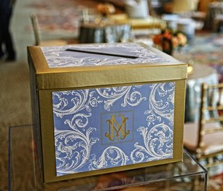 wedding-reception-with-a-golden-box-with-blue-and-white-decoration-and-couples-monogram