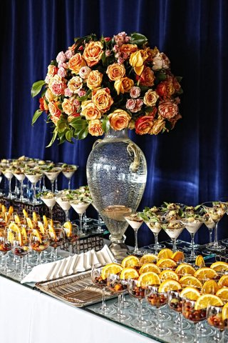 wedding-dessert-table-with-desserts-in-stemware-and-floral-arrangement-of-orange-and-pink-roses