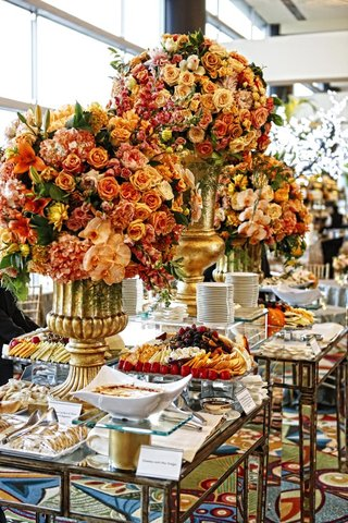 appetizer-table-decorated-with-large-golden-urns-filled-with-yellow-orange-and-red-flowers