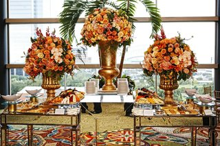 wedding-appetizer-tables-with-mirrored-panels-and-golden-urns-with-yellow-orange-and-pink-flowers