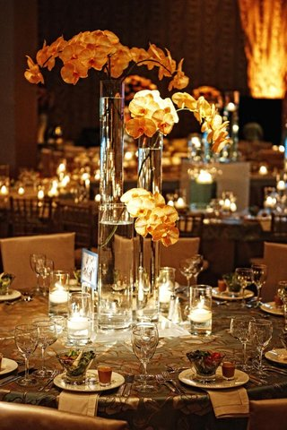 wedding-reception-table-with-three-cylinder-vases-with-orchid-stems-surrounded-by-candles