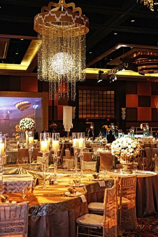 wedding-reception-with-tables-covered-in-gold-tablecloths-and-topped-with-tall-candleholders