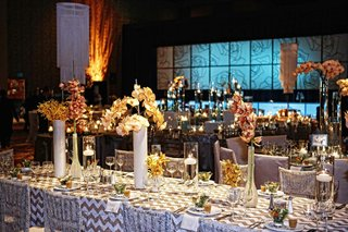 wedding-reception-table-lined-with-tall-and-low-clear-and-milky-vases-with-orchids
