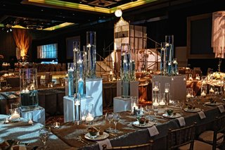 wedding-reception-tables-surround-stands-holding-tall-vases-with-floating-candles