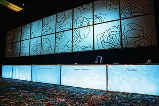 wedding-reception-buffet-with-decorative-panels-with-rose-pattern-above-and-dish-names-below