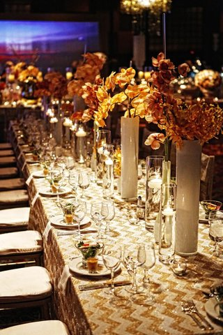 wedding-reception-table-with-gold-and-white-chevron-design-and-orchid-stems-in-milky-vases