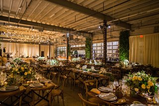warehouse-wedding-venue-rustic-decor-wood-tables-green-white-centerpieces-light-bulb-dance-floor