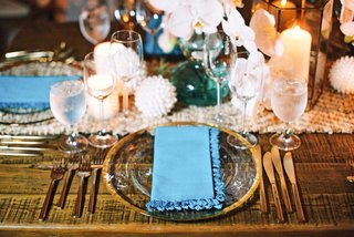 bare-wood-table-with-gold-rim-glass-charger-plate-gold-flatware-white-orchid-flowers-candles