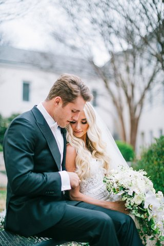 bride-in-berta-wedding-dress-cascading-white-greenery-bouquet-groom-in-suit-with-bow-tie-cuddle