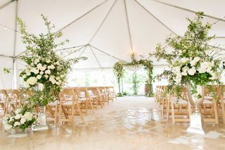tan-wedding-chairs-white-cushions-green-arch-white-flower-and-greenery-entrance-to-aisle