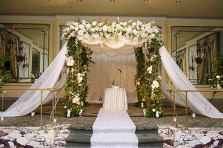 ceremony-structure-with-green-vines-and-white-flowers-and-drapery
