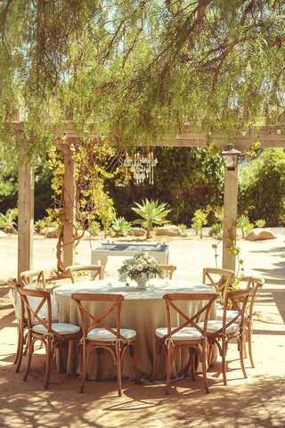 tan-linen-round-reception-table-with-wood-chairs-small-white-flower-centerpiece-courtyard-venue