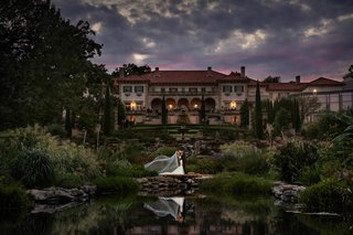 philbrook-museum-of-art-wedding-venue-brides-veil-cascading-while-bride-and-groom-kiss-by-pond