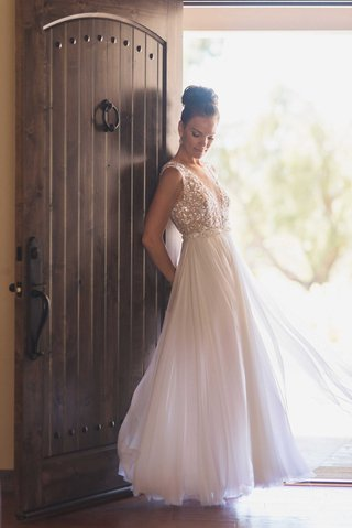bride-by-rustic-door-wearing-mira-zwillinger-sheath-wedding-dress-from-carines-bridal-atelier-bun