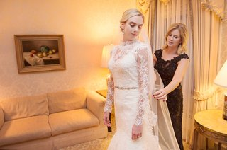 bride-in-wedding-dress-with-lace-over-top-gets-ready-with-her-mom-on-wedding-day