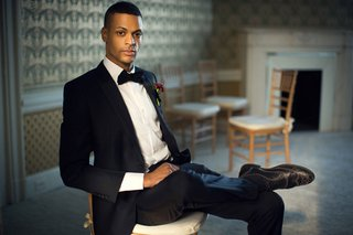 stylish-groom-sitting-chair-wedding-hempstead-house-new-york-classic-look-tux-old-world-vintage