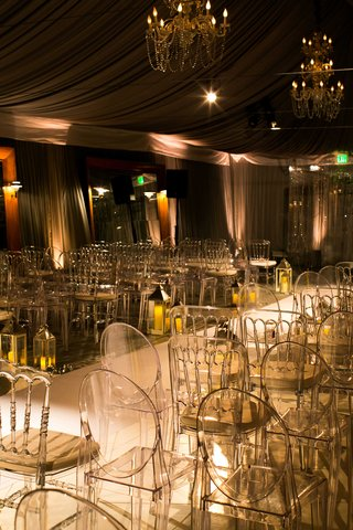 dimly-lit-ceremony-space-with-white-aisle-runner-ghost-chairs-and-small-votives-lining-aisle