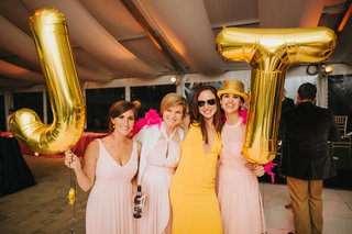 wedding-guests-holding-gold-mylar-balloons-with-bride-and-groom-initials