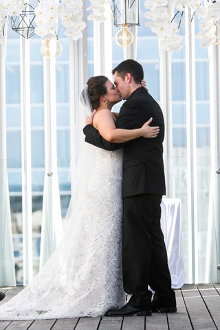 a-bride-in-white-fit-and-flare-gown-and-groom-in-all-black-tuxedo-embrace-first-kiss-married-couple
