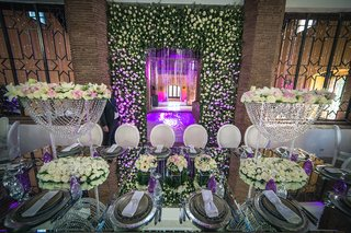 long-mirror-top-table-high-centerpieces-floral-wall-purple-uplighting-morocco-destination-wedding