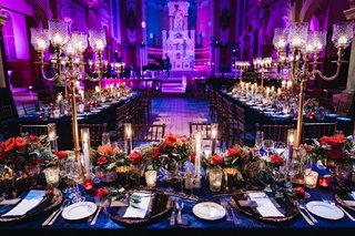 wedding-reception-bright-purple-blue-lighting-gold-candelabra-blue-linen-red-flowers-candlelight