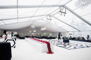 reception-tent-with-black-and-white-dance-floor-and-red-flower-runner