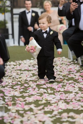 ring-bearer-in-tuxedo-carrying-corner-of-pillow-with-flowers-on-top